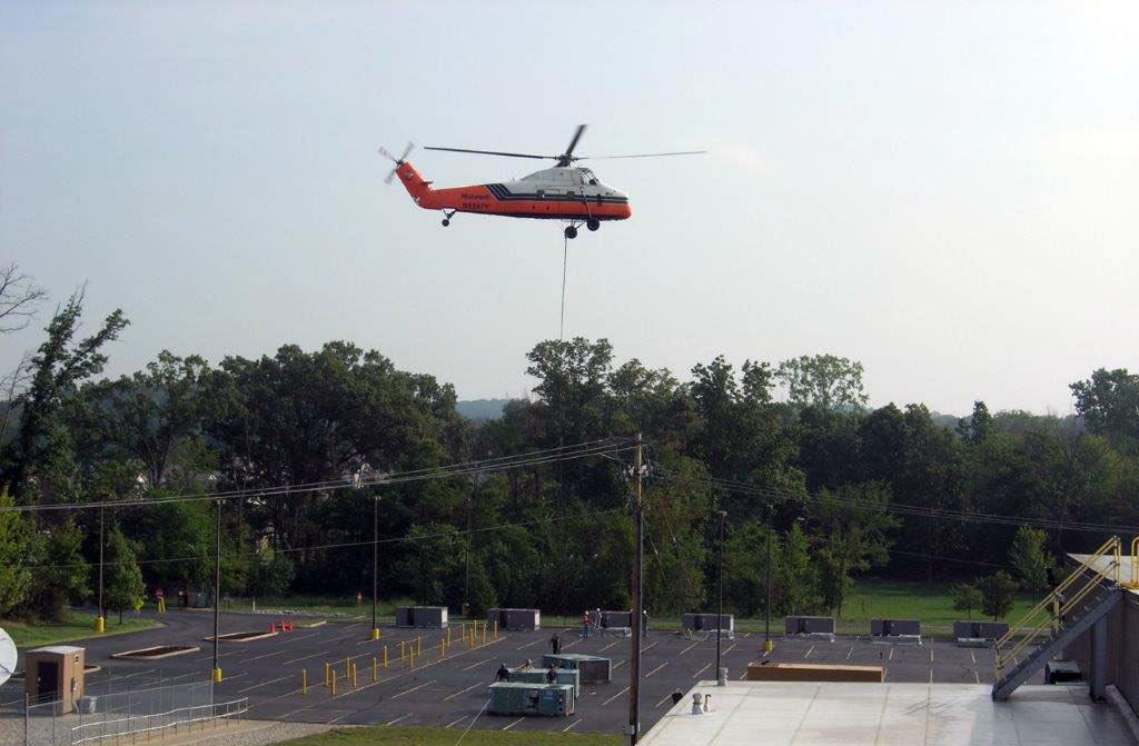 Helicopter delivering an HVAC unit