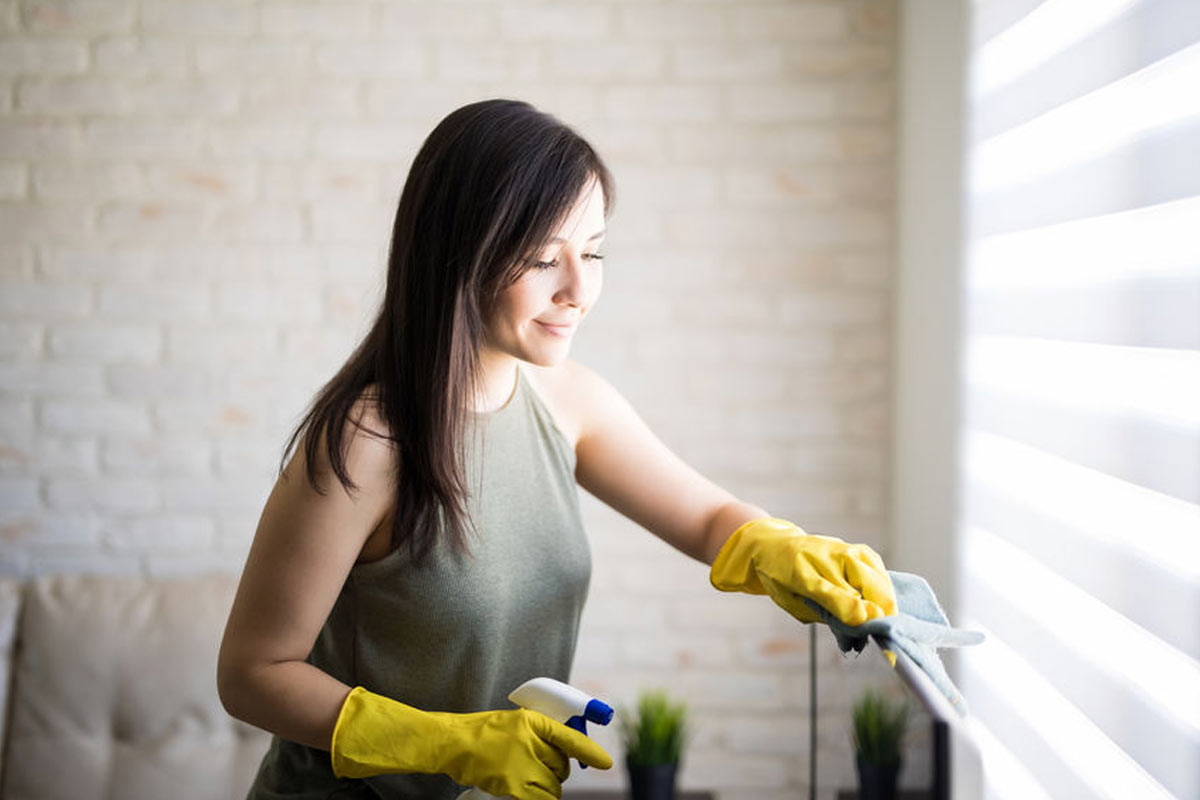 A woman wiping dust from window blinds.